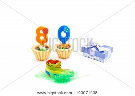 Cakes With Eighty Years Birthday Candles, Whistle And Gift On White