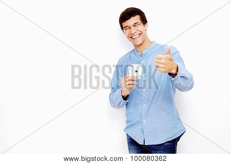Young hispanic man wearing jeans and glasses holding two aces (hearts and clubs) in his hand and showing thumb up hand gesture with smile against white wall - gambling concept