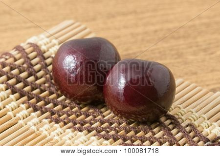 Two Red Plums On A Wooden Plate