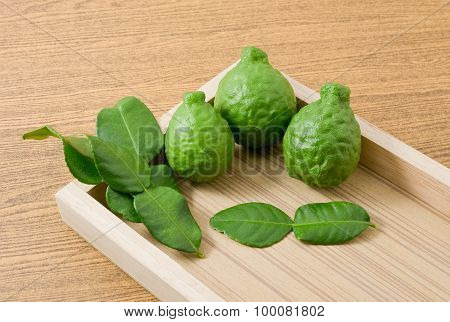 Fresh Kaffir Lime With Leaves On Wooden Tray