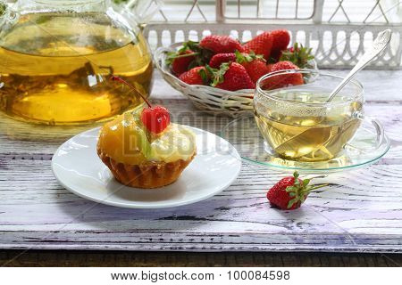 Tea In A Transparent Cup, A Cake With Fruit And A Fresh Strawberry