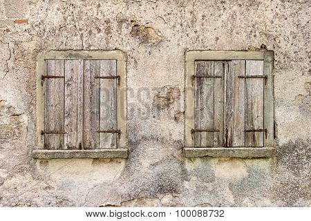 Two old windows with closed shutters