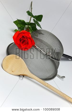 Two Kitchen Sieves With Red Rose And Wooden Spoon