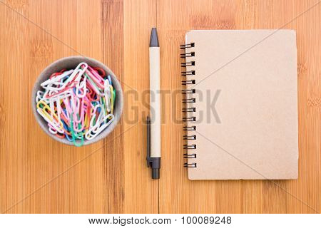 Vintage style of open notebook and pen on the old wooden floor