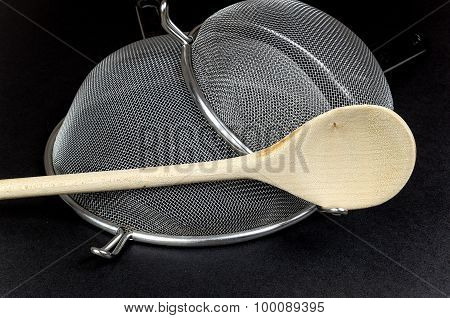 Two Kitchen Sieves With Wooden Spoon On Black Background