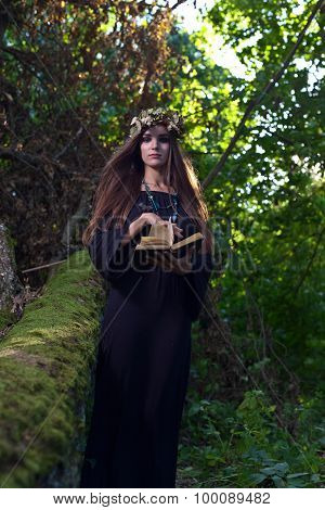 Woman With Book In Dark Forest