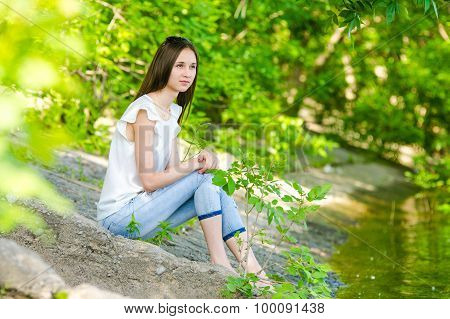A Girl Sits On The Concrete Bank Of The River