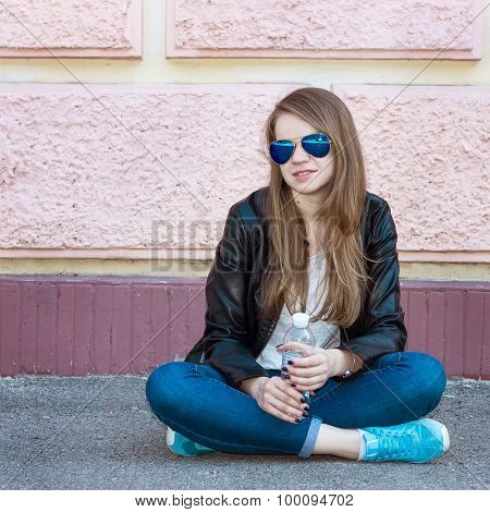 Girl In Jacket, Jeans And Sunglasses Sitting On Pavement