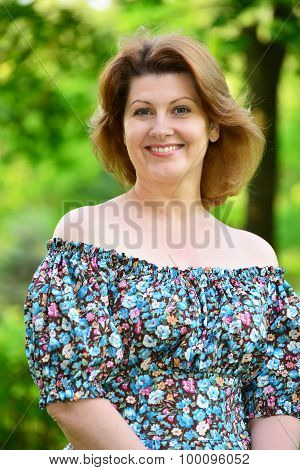 stylish middle-aged woman in the summer park