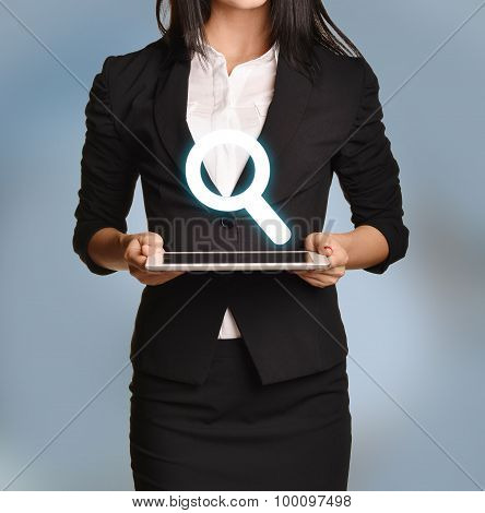 Woman is holding tablet with magnifier icon