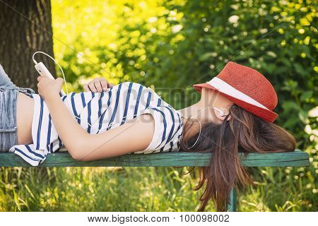 Teenage girl laying on the bench and listening music