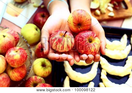 fresh ripe apples  in hands with croissant on the background