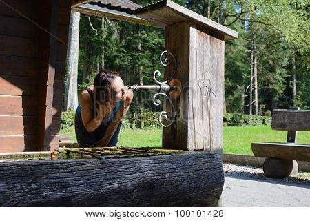 Woman drinking water from an old well