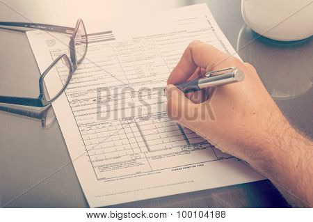 Man Filling An Health Insurance Claim Form