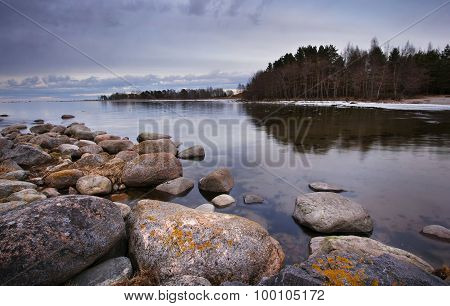 Seacoast in march with stones on the foreground
