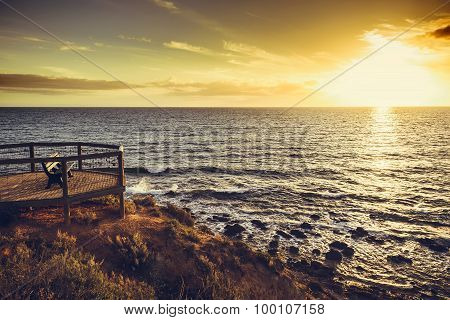 Bench On The Edge Of The Rock At Sunset