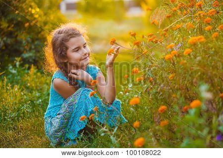 teen girl sitting on his haunches and touching orange flower in