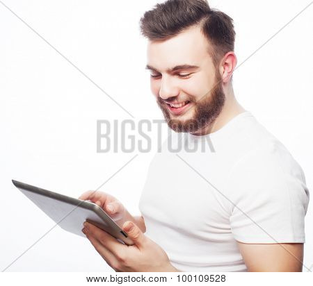 Tehnology and lifestyle concept: young man wearing white t-shirt using a tablet computer - isolated over a white background