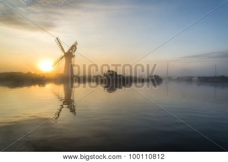 Stunnnig Landscape Of Windmill And River At Dawn On Summer Morning