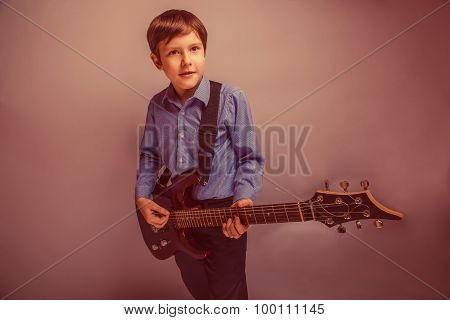 teenager boy brown hair of European appearance playing guitar ex