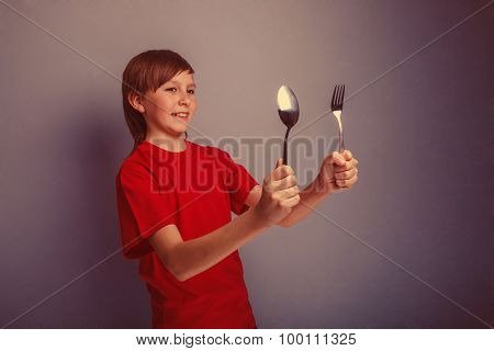 Teenager boy in red shirt twelve years holding  spoon and fork,