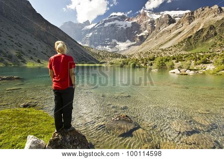 girl in red t-shirt standing near blue mountain lake