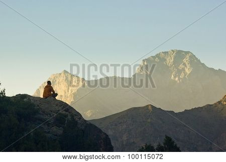 man sitting on a cliff at sunset surrounded by mountains