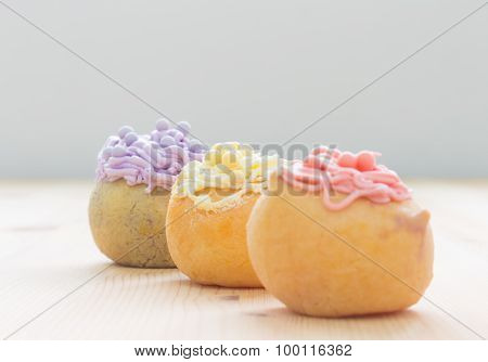 3 Color Choux Or Profiterole Or Eclair On Wood Table Oblique View