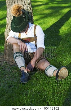 Bavarian Man Sitting By A Tree And Sleeps