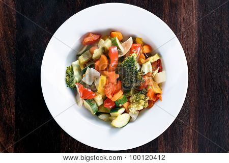 Cooked Roasted Vegetables stewed Tomatoes, Carrots, Peppers, Courgettes, brocoli, onion on plates.