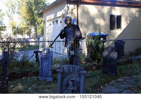 Zombie gravedigger in Halloween graveyard