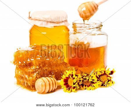 Honeycomb And Jars Of Honey With Stick And Flowers Isolated On White Background