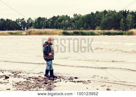 A Boy Walks Along The Lake