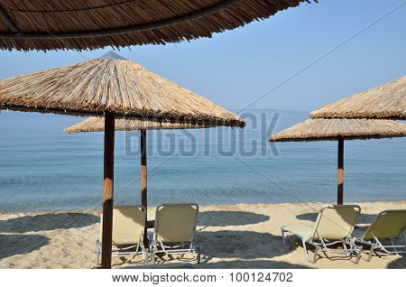Beach Straw Parasols And Pairs Of Chairs