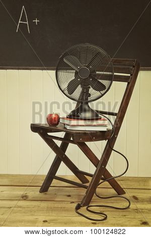 Old fan with apple and books on chair in school room