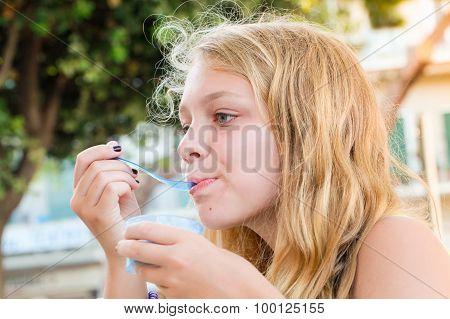 Blond Caucasian Teenage Girl Eats Frozen Yogurt