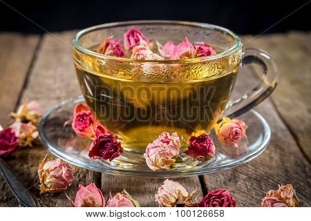 Closeup of green tea cup with dried rose buds