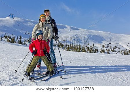 Family of three people learns skiing together