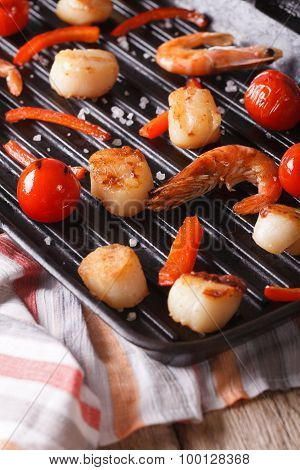 Scallops And Shrimp Are Fried On A Grill Pan Close-up. Vertical