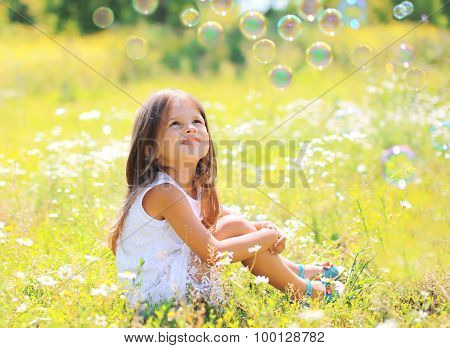 Child Sitting On The Grass Dreaming In Sunny Summer Day
