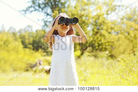 Little Girl Child Looks In Binoculars Outdoors In Summer Day