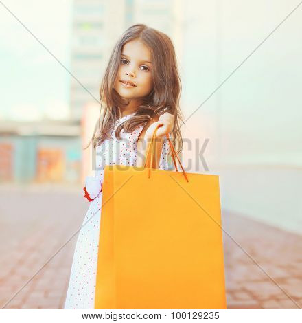 Portrait Of Beautiful Little Girl With Shopping Bag Outdoors