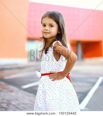 Portrait Of Cute Little Girl Wearing A Dress In The City