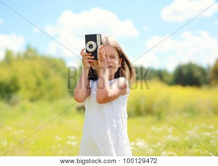 Portrait Of Little Girl Child With Retro Vintage Camera Outdoors In Sunny Summer Day