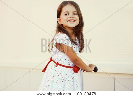 Portrait Of Smiling Little Girl On The Scooter Having Fun Outdoors