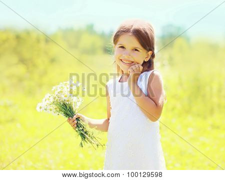 Sunny Portrait Of Cute Smiling Little Girl Child With Bouquet Of Chamomiles Flowers In Summer Day