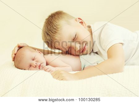 Two Children Lying Sleeping On The Bed At Home, Eldest Brother Hugging Youngest Baby