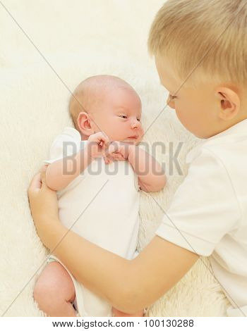 Two Children Lying Together On The Bed, Eldest Brother Hugging Youngest Baby