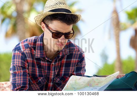 Young Male Traveler Reading Map Outside