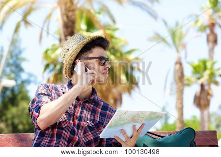 Young Male Traveler Talking On Mobile Phone And Holding Map